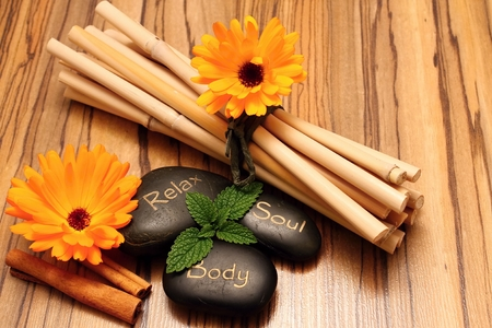 Black lava stones and flower blooms on wooden boards with cinnamon and bamboo in background Stock Photo