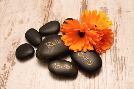 Black lava stones and marigold flower blooms on wooden boards with worn white color