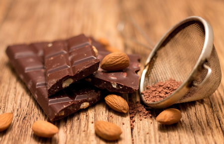 sifter: Celebration scene with dark nut chocolate is placed on old wooden board broken to pieces with almonds around and with cocoa powder in metal sifter which is near to sweets. Stock Photo