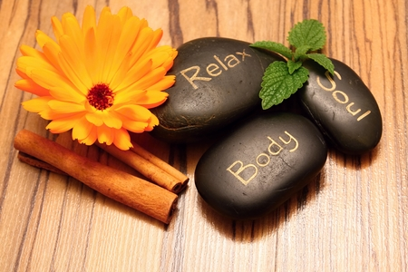 health spa: Black lava stones and flower marigold blooms on wooden boards with melissa leafs and bamboo in background placed on wooden board