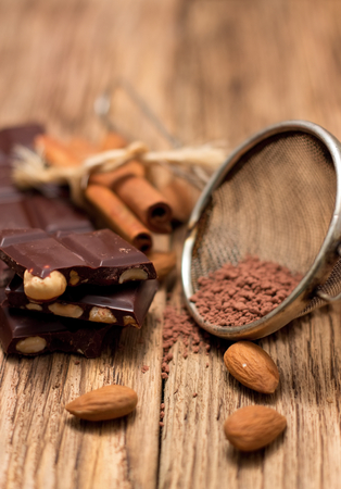 sifter: Celebration scene with dark nut chocolate is placed on old wooden board broken to pieces with almonds around and with cocoa powder in metal sifter which is near to sweets and with cinnamon in background.