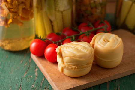 Photo of one Parenica rolled steamed cheese on wooden board which is placed on another wooden table with tomatoes near the portion and with preserved vegetable in background photo