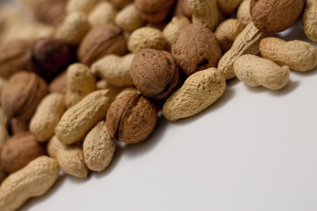 awry: Picture of heap of peanuts and walnuts in a pile captured from awry view on white table with very low depth.