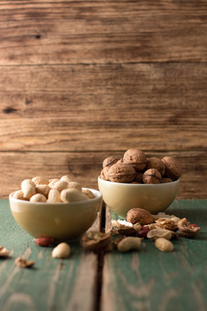 Photo of two bowls, one with walnuts and second with peanuts and with shells and nuts around.  photo