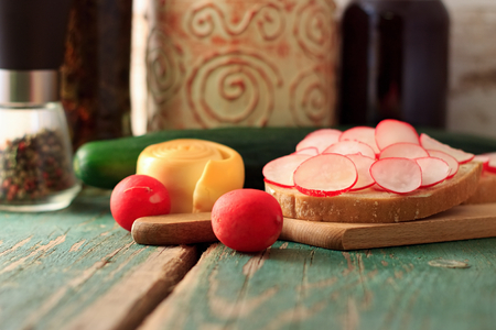 Picture of bread slice with butter and cut radishes. Steamed rolled cheese and cucumber is placed near wooden board and jam with preserved herbs are in background plus mill with color pepper. photo