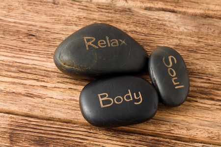 Photo of three lava stones for massage placed on old wooden board with very nice groovy texture.