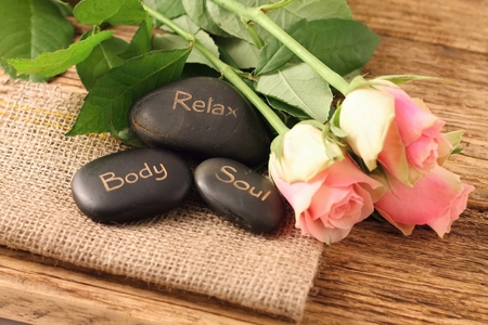 Three lava stones and three pink roses on jute cloth and old worn wooden board with very nice texture. Stock Photo