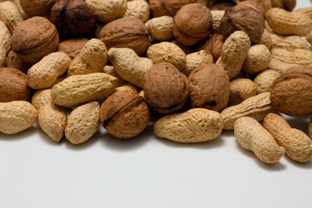 awry: Picture of heap of peanuts and walnuts in a pile captured from front view on white table with low depth.