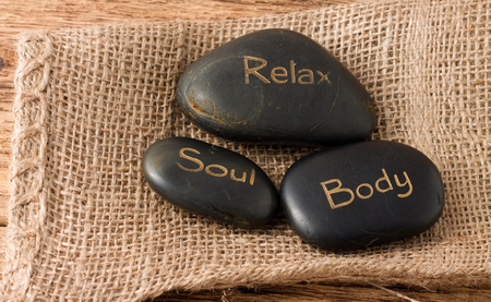 massage symbol: Picture of three lava stones Relax, Soul and Body placed on jute cloth which is on the old worn wooden board with nice texture. Stock Photo