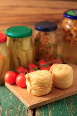Photo of two pieces smoked cheese parenica on the wooden board with tomatoes and preserved vegetable and mushrooms in background. photo