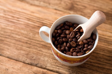bean family: Photo of Upper view on cup full of coffee grains and with wooden spoon inside placed on old wood board. Stock Photo