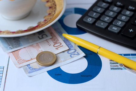 one sheet: Horizontal photo with paper sheet with printed pie chart, euro bills under coffee cup, yellow pen, black calculator and one euro coin. Photo is with blue tone.