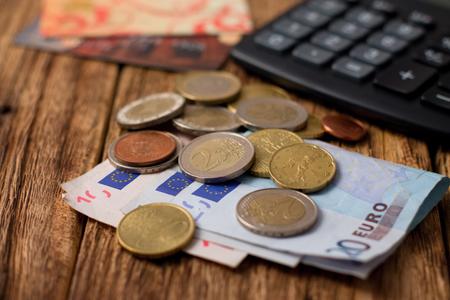 monete antiche: Foto orizzontale Pile di banconote e monete in euro e due carte di credito e calcolatrice immessi sul vecchio indossati tavola di legno Archivio Fotografico