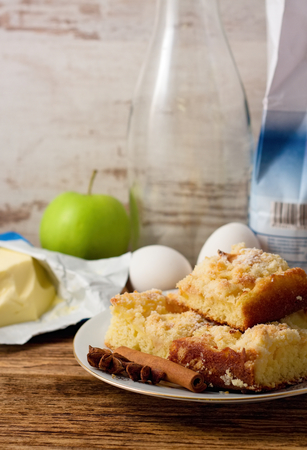 Vertical photo of Plate with several portions of apple cake on white plate with butter, apple, eggs, flour and glass bottle on old worn wooden board photo