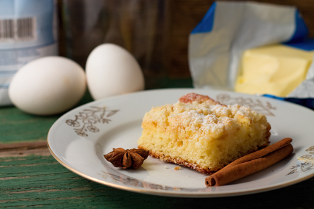spice cake: Horizontal photo of White plate with apple cake and spice, anise, cinnamon and eggs, flour, butter in background placed on old green wooden board