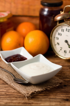 marmelade: Vertical photo of White bowl with yogurt placed on jute cloth and with second bowl with fruit with oranges, marmelade, honey and old clocks in background