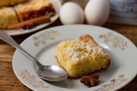 Horizontal photo of Anise star in front of apple pie placed on white plate with small spoon on right and eggs in background photo