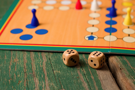 Horizontal photo of Two wooden dices in front of ludo with figurines. Dices have numbers five and six up and all is placed on green old worn wooden board. photo