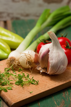 paprica: Vertical photo of Garlic, spring onion and cress on wooden board which is placed with other vegetable - tomatoes and paprica on green table