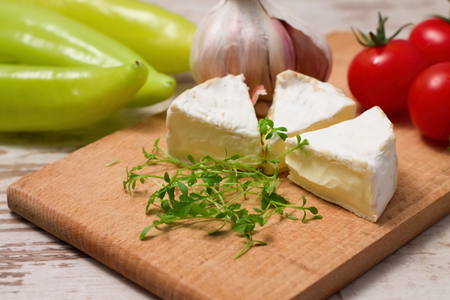paprica: Horizontal photo of Three portions of camembert and cress on wooden board with tomatoes, garlic and paprica in background all placed on white table