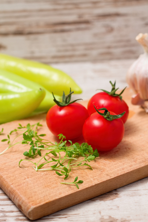 Vertical photo of Three tomatoes and cress on wooden board with onion and paprica in background all placed on white table photo