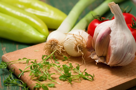 paprica: Horizontal photo of garlic bud and spring onion on chopping board. Cress shoots in front and paprica in background. All placed on green wooden table with worn color. Stock Photo