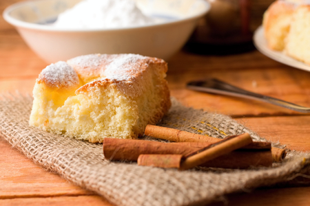Horizontal photo of single portion of curd fresh cake on jute cloth together with few pieces of cinnamon. Powder sugar in white bowl and spoon in background. All placed on wooden table. photo