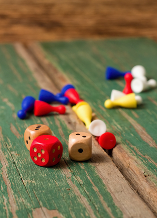 Vertical photo of three dices in front of other color figurines for ludo game. All pieces are placed on old wooden table with worn green color. photo