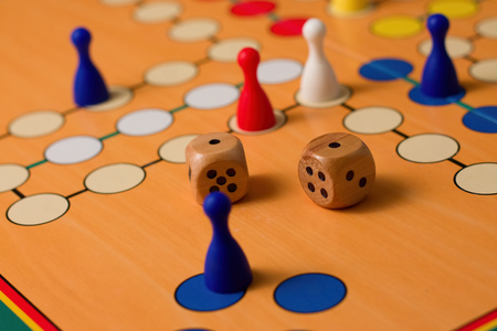 Horizontal photo of couple of wooden dices with number one up on ludo paper board with few figurines on positions for game in different colors