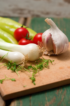 Vertical photo of Two heads of spring onion on chopping board with cress around and garlic, tomatoes and peppers in background. All on green wooden table. photo