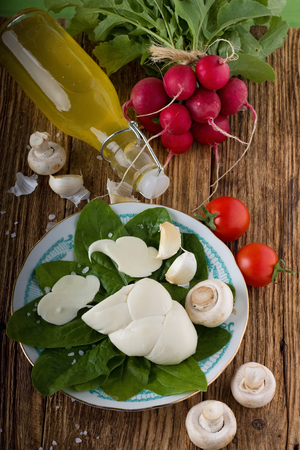 Vertical photo of traditional twisted slovak cheese on cutting board plus various vegetable around as onions, garlics, mushrooms and radishes with baby spinach with bottle with homemade lemonade. All is on wooden table. photo