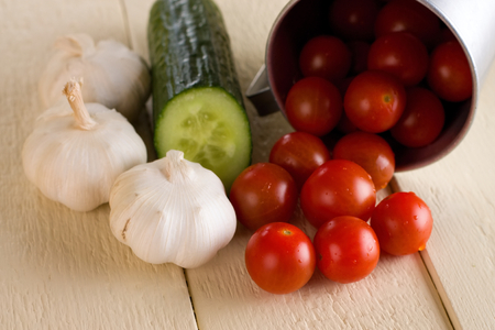 thee: Horizontal photo of several red cherry tomatoes spilled from aluminum cup together with thee garlics and single cucumber on old table with white color. Stock Photo