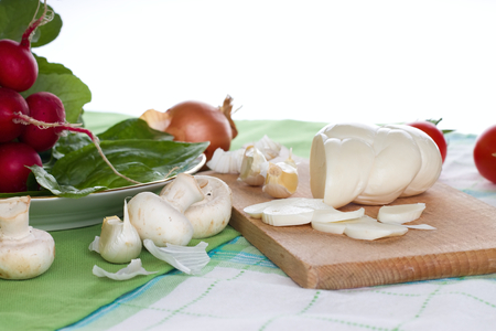 Horizontal photo of various vegetable on green cloths plus traditional slovak twisted cheese on wooden chopping board plus few slices cut. photo