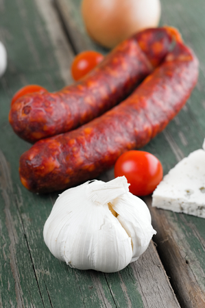 all right: Vertical photo of whole white garlic head in front of two sausages tomatoes and onion. All is placed on old green table. Piece of danish blue cheese is on right. Stock Photo