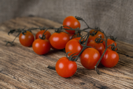 unwashed: Horizontal photo of Dirty brunch of cherry tomatoes just harvested and unwashed. Fruit is placed on wooden board table with jute cloth around. Stock Photo