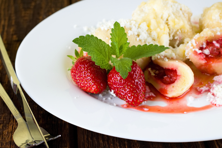 Horizontal photo with detail of two fresh strawberries on white plate. Fruit dumplings with sugar are placed on plate plus few leaves of green herbs. Plate is placed on wooden table with fork and knife. Stock Photo