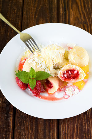 Vertical photo with fruit dumplings sprinkled by curd and sugar. Couple of strawberries and herb leaves are near the edge and single fork is leaning against plate. All is on wooden board.