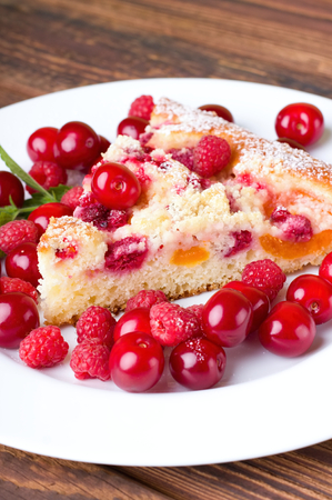 side plate: Vertical photo of fruit pie on white plate among heap of red juicy cherries and sweet raspberries. Single branch of melissa is placed on side. Plate is on wooden board.
