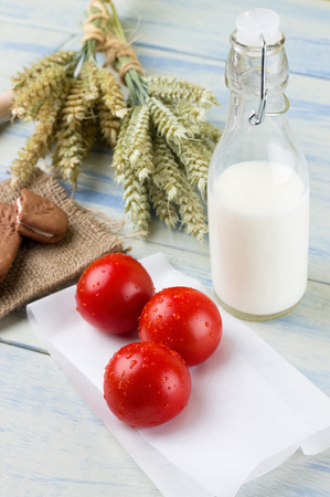 bonded: Vertical photo of three dewy cherry tomatoes on paper sheet in front of glass bottle of milk, few cereal biscuits on burlap and grain ears bonded by cord. All is on light blue wooden board. Stock Photo
