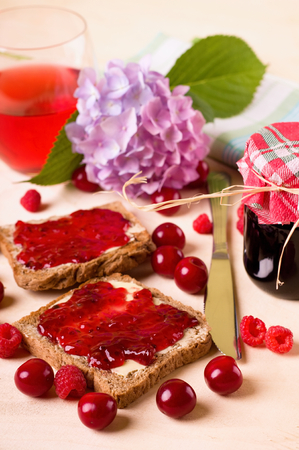 sweet food: Vertical photo of couple of toasts with butter and homemade marmalade from cherries and raspberries which are around with knife, jar and hydrangea bloom on light wood table.
