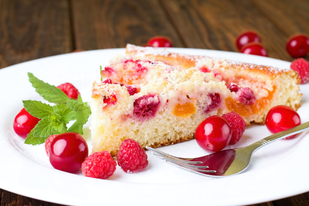 a portion: Horizontal photo of single portion of fruit pie with cherries and peaches placed on white plate together with raspberries and other cherries. Green herb and fork are there too.