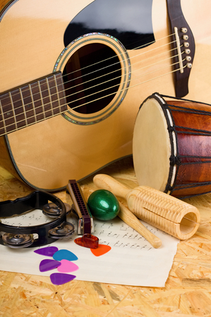 bongo: Vertical photo of several music instruments as bongo, acoustic guitar, harmonica, rattles and few picks on paper sheets with notes. All is placed on wooden OSB board.