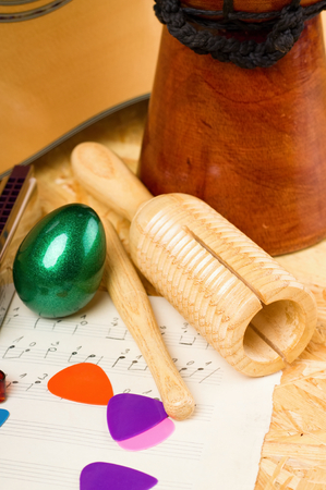 shekere: Vertical photo of wooden guiro and green egg shaker on piece of paper with written music. Bongo, acoustic guitar and few picks are around on OSB board. Stock Photo