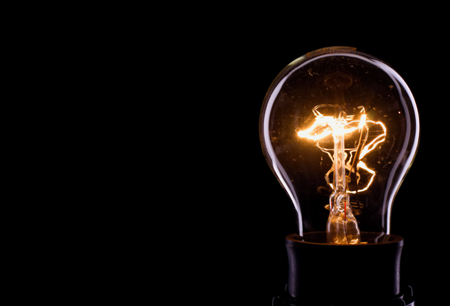 Horizontal photo of a bulb on black background. Only outline of a glass bulb is visible and inner part with lighted wire is there.