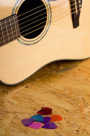 picks: Vertical photo of an acoustic guitar with golden strings and made from solid light spruce. Few color picks are in front of guitar placed on wooden OSB board.