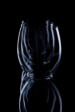 overlapped: Vertical photo of three glasses in a row which are fully overlapped. Glasses are on the black background with visible shape and nice reflection in bottom part.