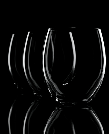 ia: Vertical photo of tree glasses in a row with small overlapping. Each glass ia smaller that the previous one. Only contours are visible with nice reflection on the bottom. Background is black.