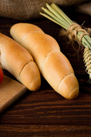 bonded: Vertical photo of two fresh rolls on a wooden table with bundle of corn bonded by natural cord.