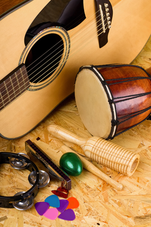 picks: Vertical photo with set of musical instruments on wooden OSB board as green egg shaker, guiro, bongo drum, few guitar picks, harmonica and acoustic guitar.
