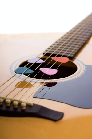 fretboard: Vertical photo of front side of acoustic guitar with bridge, strings and fretboard. Four colorful guitar picks are placed in strings over the hole in spruce board.